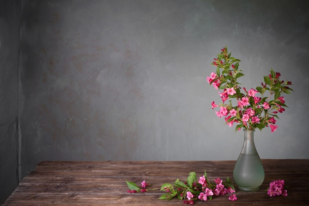 Цветы вейгелы в стеклянной вазе на деревянном столе