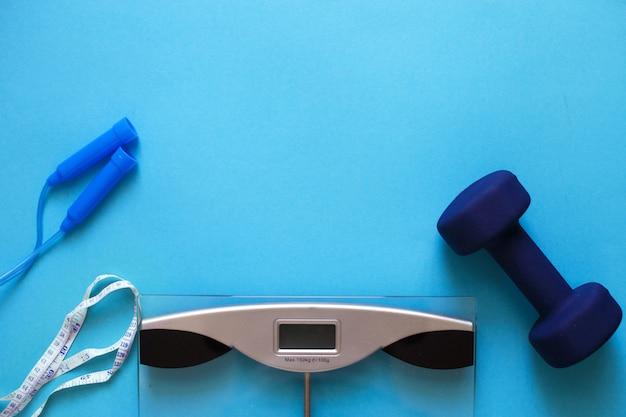 青い背景に分離されたロープとダンベルをスキップして体重計