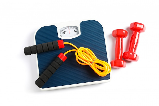 Weigh scales, skipping rope and dumbbells isolated on white