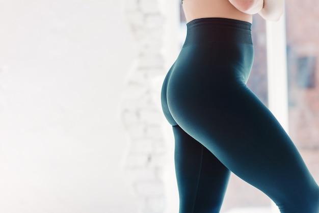 영양 활력 개념을 먹는 tloss 웰빙의 무게. 파란색 꽉 바지 레깅스를 입고 성적 스포티 한 낚시를 좋아하는 유혹 아름다운 매력적인 좋은 둥근 엉덩이의 자른 클로즈업보기 사진
