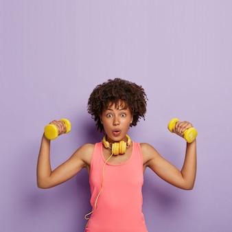체중 감소 및 운동 개념. 곱슬 머리를 가진 놀란 어두운 피부의 여성, 덤벨 올리기, 근육 훈련, 쉬운 팔뚝 운동, 캐주얼 핑크 탑 착용, 헤드폰 사용