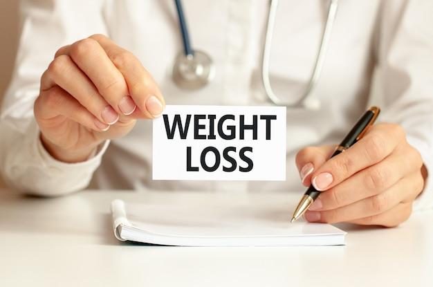 의사의 손에 체중 감량 카드. 의사의 손에 텍스트 체중 감소, 의료 개념 종이 한 장.