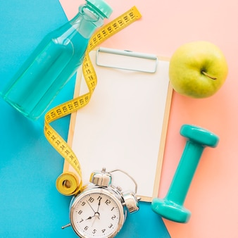 Weight loss composition with clipboard, tape measure and bottle
