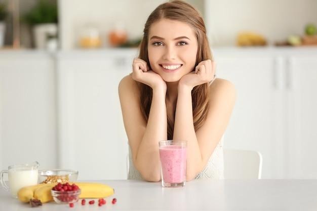 Концепция потери веса. красивая молодая женщина со здоровым вкусным смузи на кухне