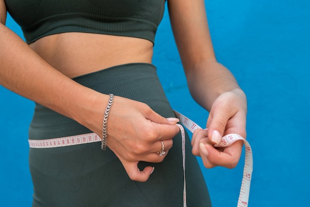 Weight loss concept, slim woman measuring her thin waist over blue background. healthy lifestyle concept