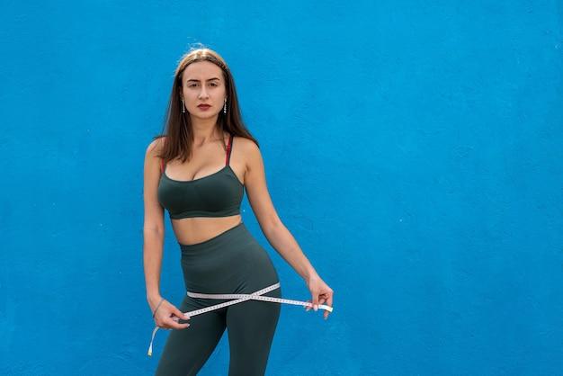 減量の概念、青い壁の上の彼女の細い腰を測定するスリムな女性。健康的なライフスタイルの概念