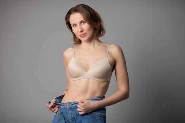 減量のコンセプトです。若い女性は彼女の減量と彼女の古いジーンズを着ています。彼女がどのように減量していたかを示す大きなジーンズでスリムな女性