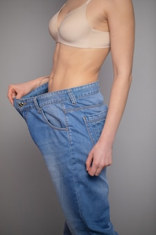Weight loss concept. young woman shows her weight loss and wearing her old jeans. slim woman in big jeans showing how she was losing weight