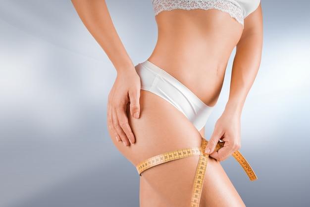 흰색 란제리에 젊은 매력적인 여자와 체중 감량 다이어트 개념. 그녀의 허벅지 주위에 테이프를 측정하고 포즈