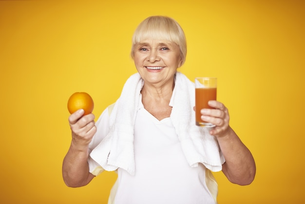 Weight loss elderly fitness woman holds orange.