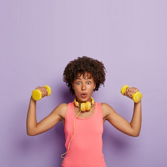 Weight loss and exercising concept. surprised dark skinned woman with curly hair, raises dumbbells, trains muscles, has easy biceps exercise, wears casual pink top, uses headphones