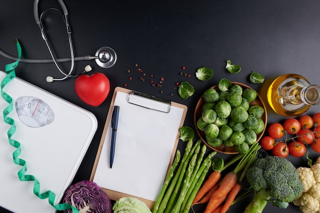 Weight loss scale with centimeter, stethoscope, dumbbell, clipboard, pen. diet concept.