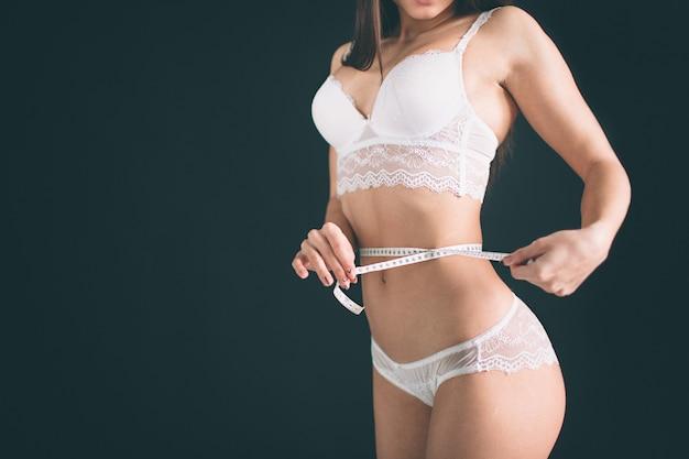 減量、スリムなボディ、健康的なライフスタイルのコンセプト。測定テープで彼女のウエストを測定するフィットネス女の子に合います。女の子はスポーツフィギュアで、白い下着を着ています。