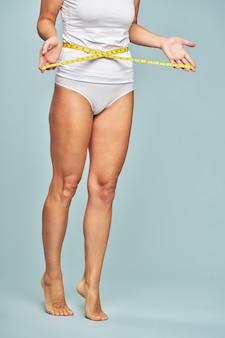 立っている間に巻尺で彼女の腰を測定している女性の減量垂直ショット