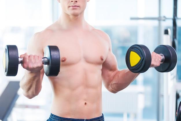 ウェイトトレーニング。ジムに立っている間ダンベルで運動している若い筋肉の男性のトリミングされた画像