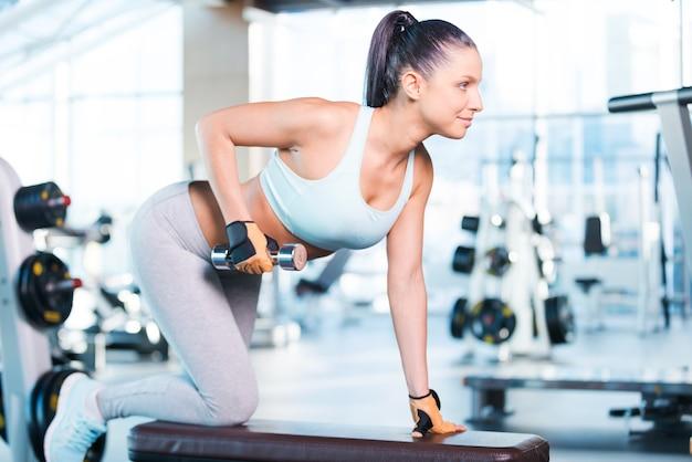 Силовые тренировки. вид сбоку уверенно молодой женщины, тренирующейся с гантелями в тренажерном зале