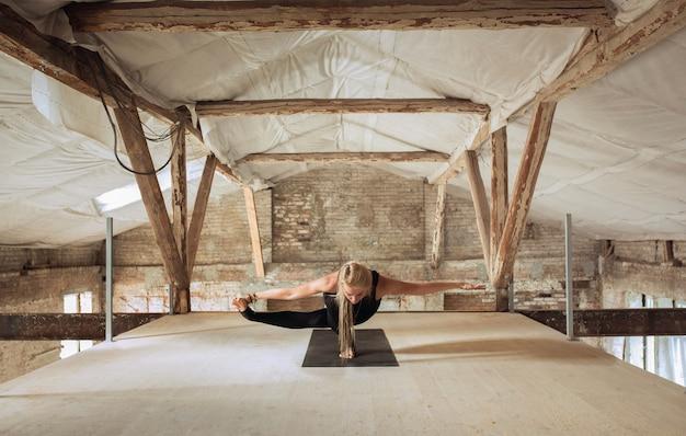 무중력. 젊은 체육 여자 버려진 된 건설 건물에 요가 연습. 정신적 및 신체적 건강 균형. 건강한 라이프 스타일, 스포츠, 활동, 체중 감소, 집중력의 개념.