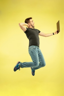 Weightless. full length portrait of happy jumping man with gadgets isolated on yellow background