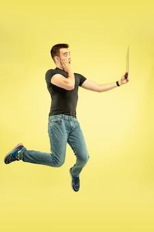 무중력. 노란색 배경에 고립 된 가제트와 함께 행복 점프 남자의 전체 길이 초상화. 현대 기술, 선택의 자유 개념, 감정 개념. 비행 중 셀카 또는 동영상 블로그에 태블릿을 사용합니다.