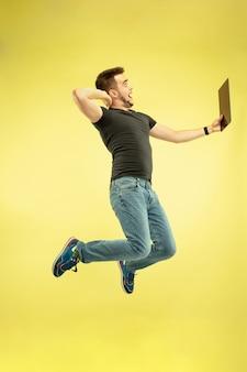 무중력. 노란색 배경에 고립 된 가제트와 함께 행복 점프 남자의 전체 길이 초상화