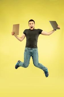 무중력. 노란색에 고립 된 가제트와 함께 행복 점프 남자의 전체 길이 초상화.