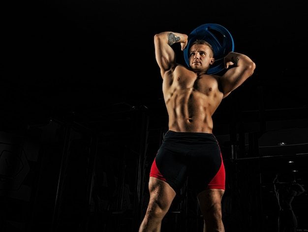 The weightlifter does the workout with burdening. he lifted a heavy pancake over his head and makes circular movements with his hips.