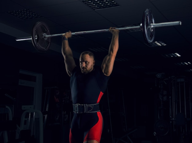 Weightlifter lifts the bar above his head. strength training with a huge weight