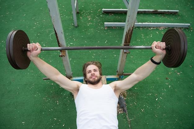 Тяжелая атлетика, бодибилдинг, фитнес, спорт. культурист поднимает штангу на стадионе. человек с атлетическим торсом, тренировка сильных рук с отягощением. мощность, энергия, концепция силы