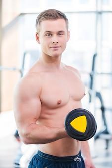 ジムでの重量挙げ。ジムに立っている間ダンベルで訓練するハンサムな若い筋肉の男