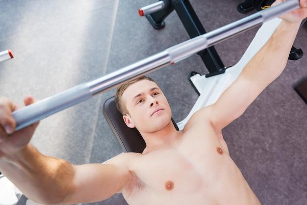 ジムでの重量挙げ。ベンチプレスで働いている自信を持って若い筋肉の男の上面図