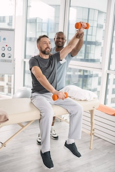 ウェイトトレーニング。素敵な快適なひげを生やした男性が医療用ソファに座って、ダンベルで腕を持ち上げる