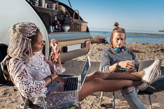 Странная прическа. светловолосый мужчина со странной прической разговаривает со своей привлекательной девушкой, сидящей возле компактного трейлера Premium Фотографии