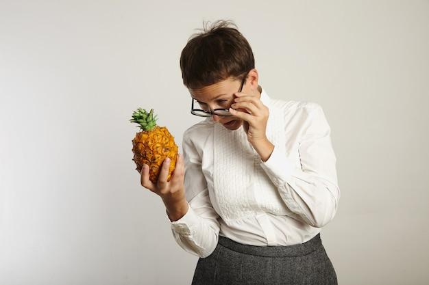 Insegnante femminile dall'aspetto strano che strizza gli occhi a un ananas sopra i vetri isolati su bianco