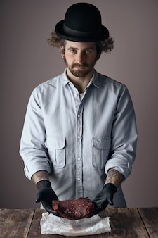 Weird young jewish butcher man with curly hair and beard wearing a too small derby hat and faded denim shirt offers a kosher raw steak in his hands on a wooden table.