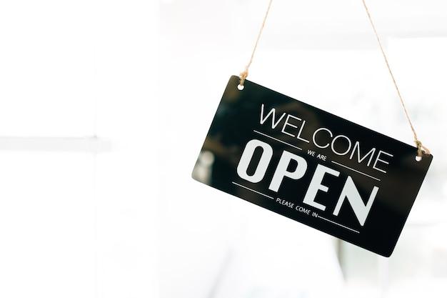 透明なインテリアホワイトのカフェのドアのガラス越しにウェルカムアンドオープン看板