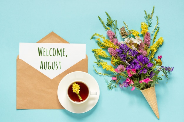 Welcome august text on paper card in craft envelope, cup of tea and bouquet field flowers in waffle ice cream cone on blue