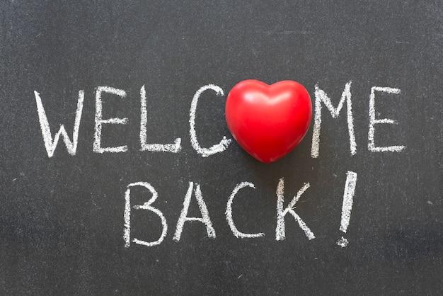 Добро пожаловать обратно фразу, написанную от руки на доске с символом сердца вместо o