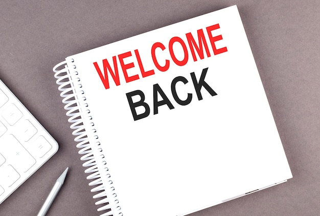 Welcome back text on notebook with calculator and pen