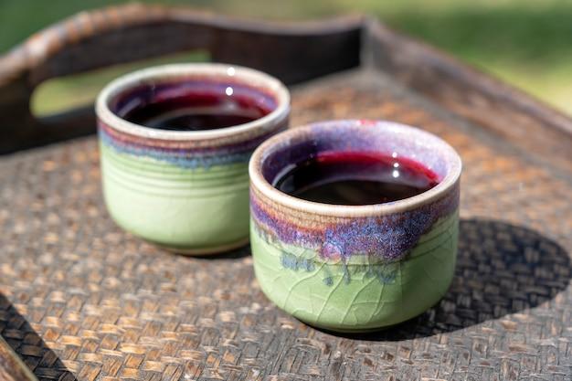 태국 코팡안 섬에 있는 호텔에서 로젤 주스와 함께 웰컴 드링크를 제공합니다. 쟁반에 있는 세라믹 컵에 두 잔, 클로즈업