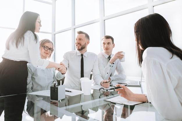 オフィスのデスクトップ近くの握手従業員を歓迎します