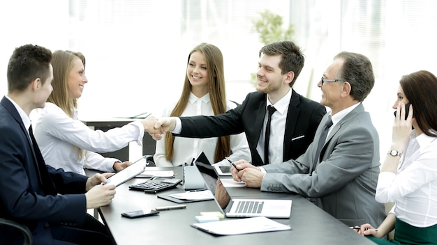 사무실의 협상 테이블에서 비즈니스 파트너의 악수를 환영합니다.