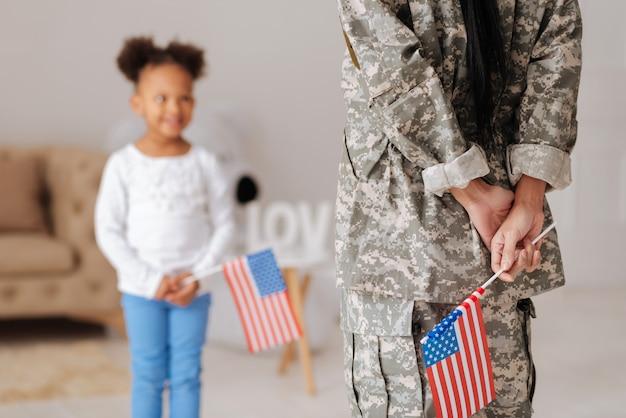おかえりなさい。リビングルームに立って旗を手に持って抱きしめるお母さんを待っているカリスマ的な可愛い女の子