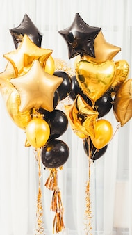 Welcome home party decoration. golden and black round, heart, star shaped balloons on white.
