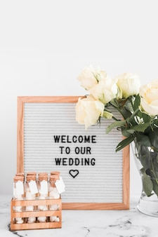 Welcome message for wedding on white frame with marshmallow test tubes and rose vase