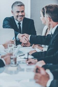 Добро пожаловать на борт! уверенный в себе зрелый мужчина в строгой одежде, пожимая руку одному из своих коллег и улыбаясь, сидя за столом вместе