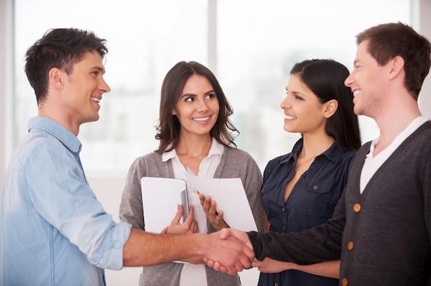 Добро пожаловать на борт! два веселых молодых человека обмениваются рукопожатием, в то время как две женщины смотрят на них и улыбаются