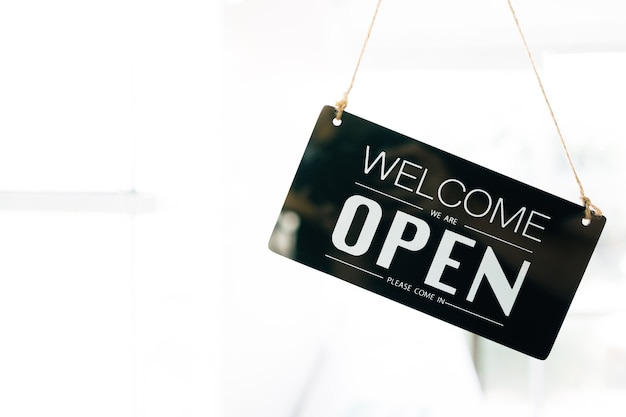 Welcome and open sign board through the glass of door in the cafe with clear interior white
