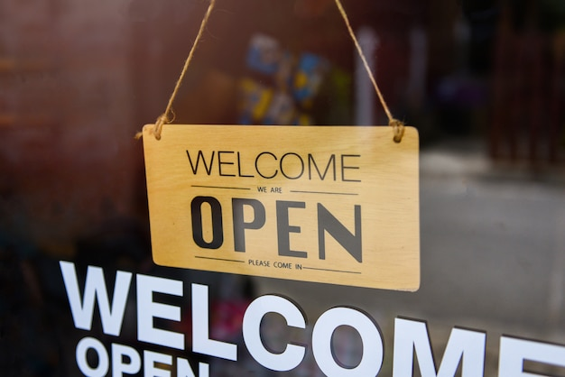 Welcome open sign hanging on cafe glass door