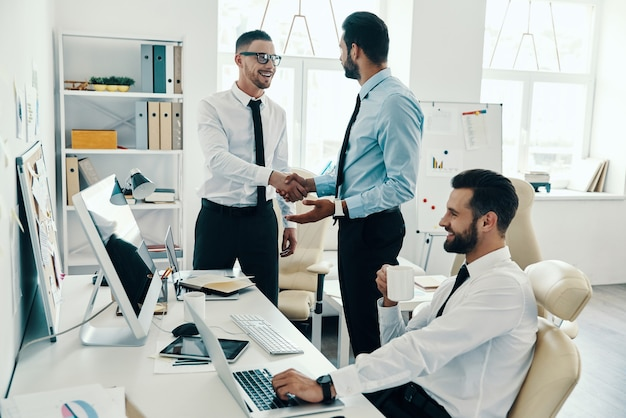 Welcome to our team! young modern men in formalwear shaking hands while working in the office