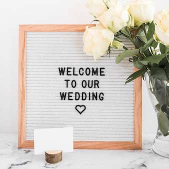 Welcome to our wedding message on wooden frame with blank visiting card and roses